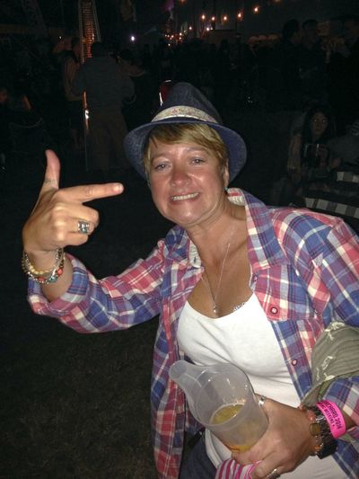 Festival fun Woman In A Hat And Check Shirt Holding A Drink Little Ochard Cider And Music Festival Evening Dark Cider And Music Festival Festival Being Silly Humour Night Arts Culture And Entertainment Front View One Person Adult Smiling Waist Up Happiness Music Event Nightlife Clothing 2018 In One Photograph