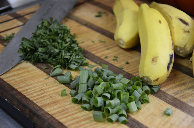 Close-up of chopped spring onions with coriander and bananas on cutting board