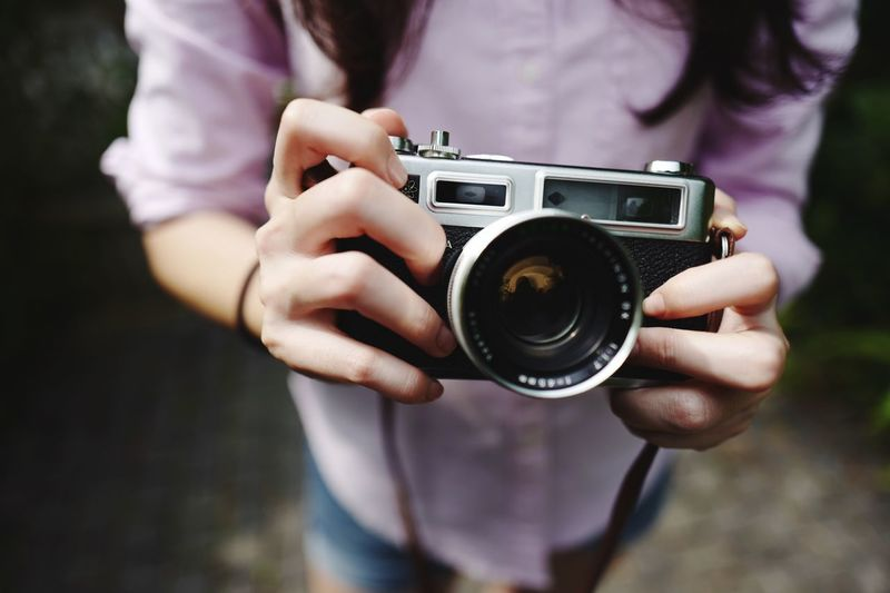 Vintage Camera Hobby Film Camera Vintage Camera Photography Themes Camera - Photographic Equipment Midsection Real People One Person Holding Technology Photographing Focus On Foreground Photographic Equipment Activity Front View Leisure Activity Occupation Lifestyles Day Camera Women Photographer Modern
