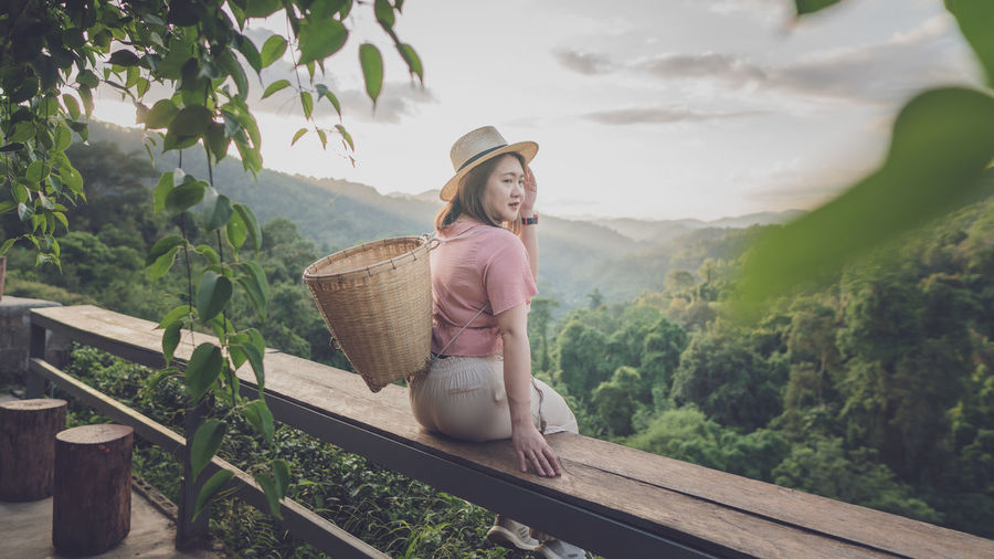 Woman carrying basket while sitting on railing