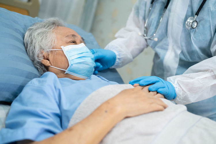 Midsection of doctor consoling patient wearing flu mask at hospital