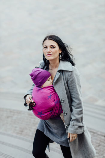Babywearing mother carrying her child in woven wrap. Portrait of young fashionable woman hugging her sleeping child in sling. Baby Babywearing Motherhood Carry Carrier Wrap Sling Child Infant Wear Attachment Parenting Woman Relationship Bonding Closeness Togetherness Together Woven Caucasian Love Ergonomic City Safety Three Quarter Length