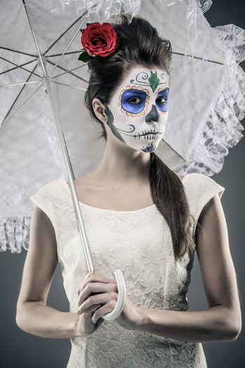 Day of the dead girl with sugar skull makeup holding lace umbrella Day Of The Dead Halloween Horror Makeup Mexican Culture Mortality Woman Body Arts Calavera  Caucasian Culture Day Of The Dead Skull Female Girl Hairstyle Lace Umbrella Macabre Art Mexican Holidays One Person Portrait Red Rose Skeleton Makeup Sugar Skull Voodoo Young Adult