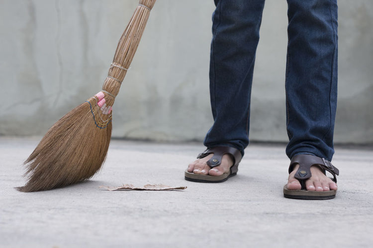 Low section of man sweeping footpath with broom against wall