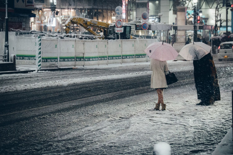 People with umbrellas standing on snow in city