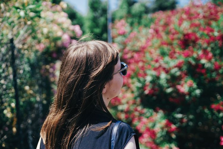 Close-up of young woman with sunglasses against trees