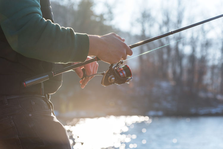 Close-up of hand holding fishing rod over lake