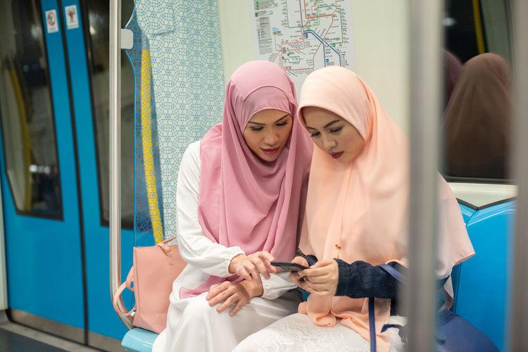 Women sharing mobile phone sitting in metro train