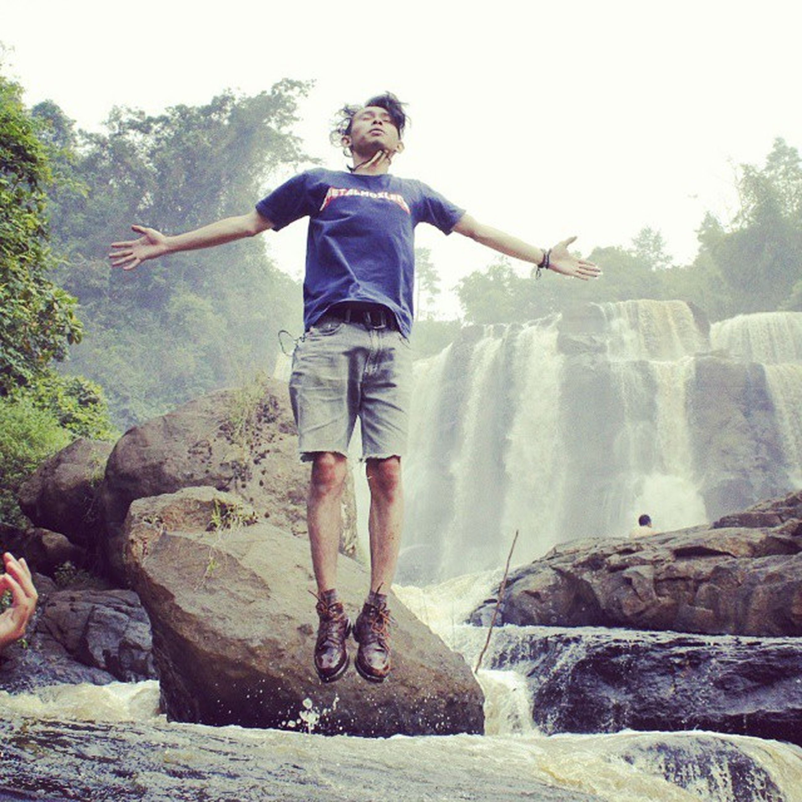 lifestyles, leisure activity, full length, young adult, casual clothing, person, young men, standing, arms outstretched, front view, portrait, vacations, looking at camera, water, low angle view, rock - object, happiness
