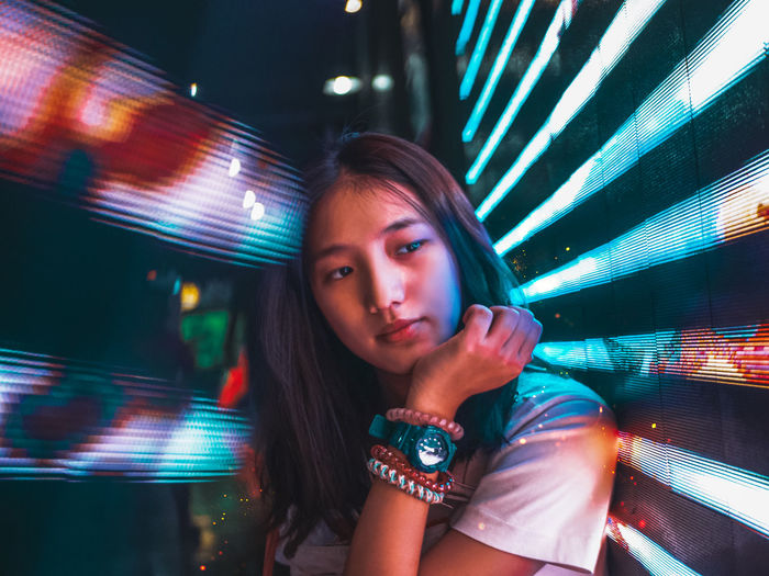 Portrait of young woman in illuminated carousel at night