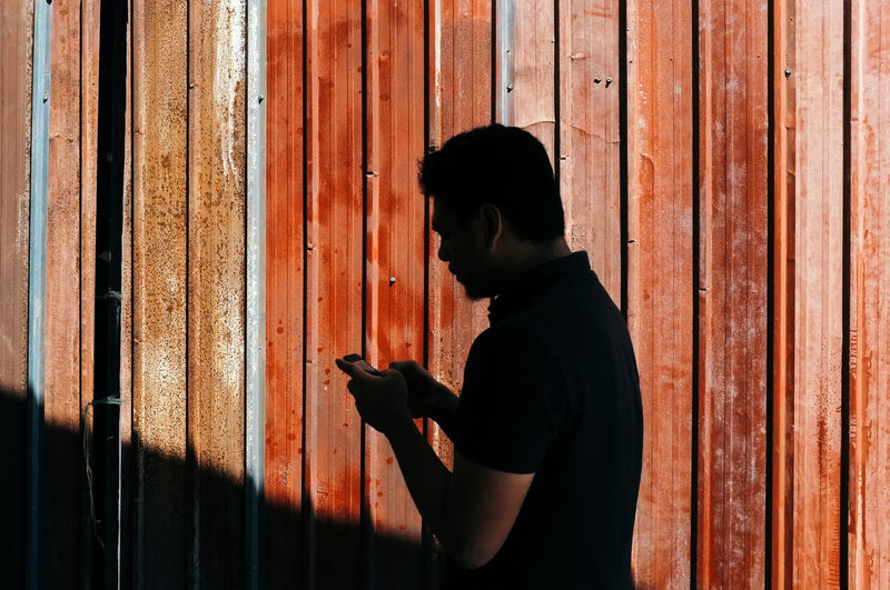 Side view of man using mobile phone against rusty metal
