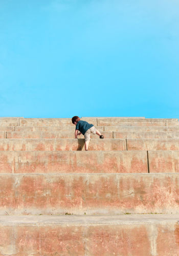 Full length rear view of boy climbing steps against clear blue sky