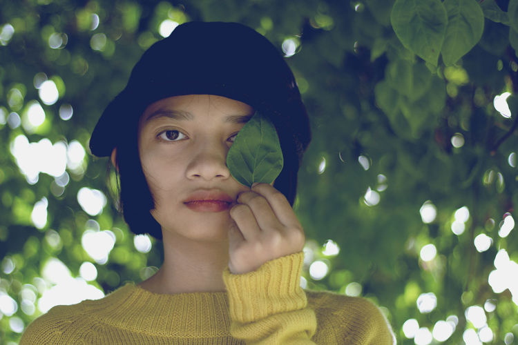 Close-up portrait of teenage girl holding leaf against trees
