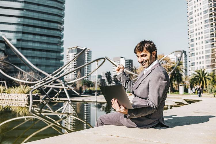 Smiling businessman using laptop while sitting at park