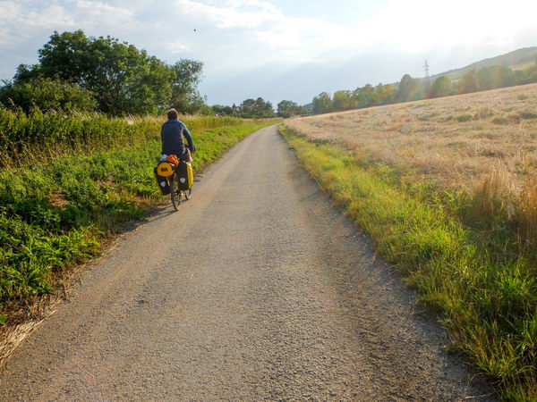 Adventure Bicycle Bike Packing Bike Touring Cycling Day Field Full Length Grass Growth Landscape Leisure Activity Lifestyles Nature One Person Outdoors Real People Rear View Riding Road Rural Scene Scenics Sky The Way Forward Transportation