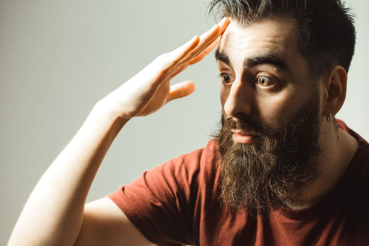 Close-up of shocked man against gray background
