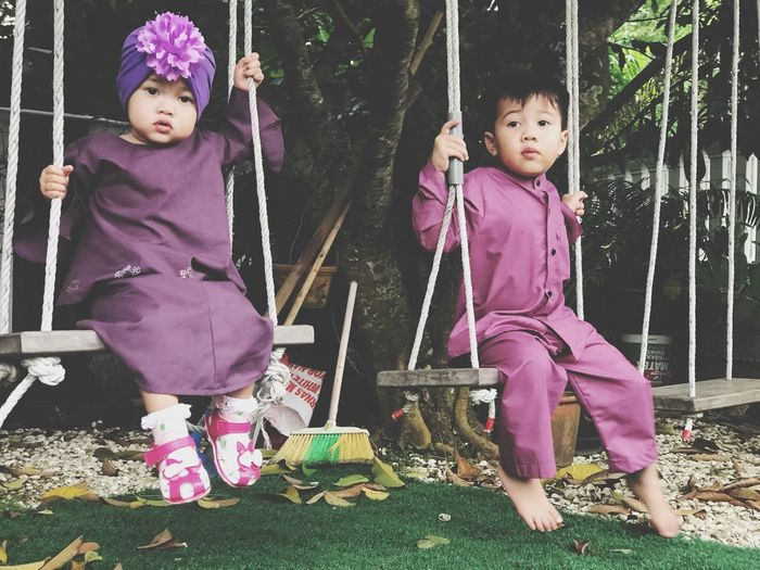 Full length of cute siblings in traditional clothing swinging against trees at park