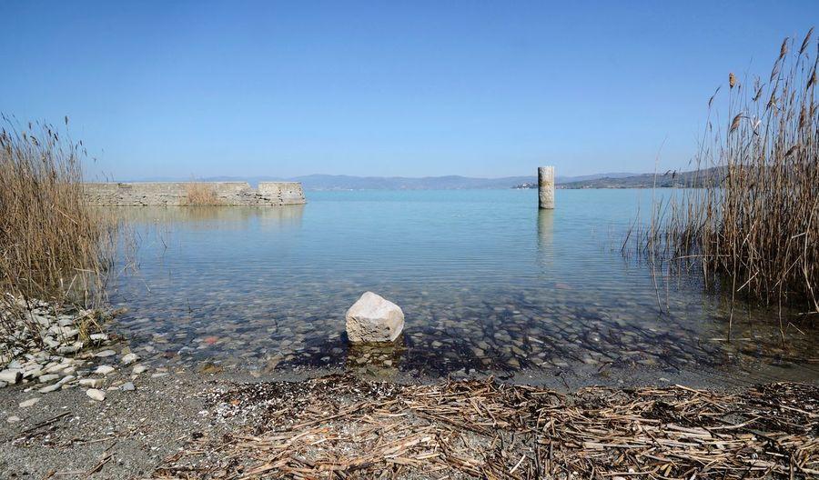Scenic view of italian Trasimeno lake coastline on a sunny day Umbria Trasimenolake Rocks Stone Water Beach Clear Sky Sky Calm Shore Horizon Over Water Sandy Beach Pebble Beach Sand