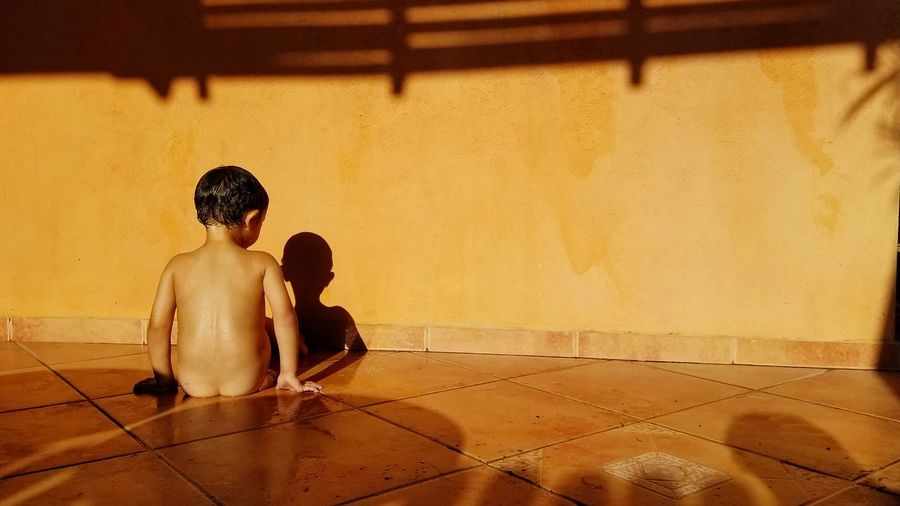 Rear view of naked boy sitting on floor at home