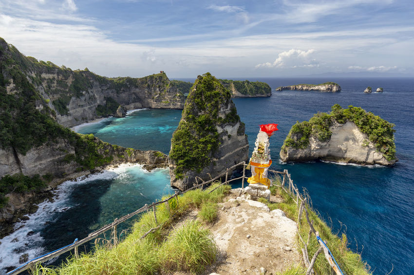 Small Raja Lima islands with a beautiful shrine in the foreground on Nusa Penida in Indonesia. ASIA Atuh Beach Bali Diving Hindu INDONESIA Indonesian Nusa Batupadasan Shrine Tourist Travel Ampoak Atuh Balinese Beach Destination Klungkung Landscape Lebah Nusa Batumategan Nusa Penida Pejukutan Raja Lima Tourism Tropical