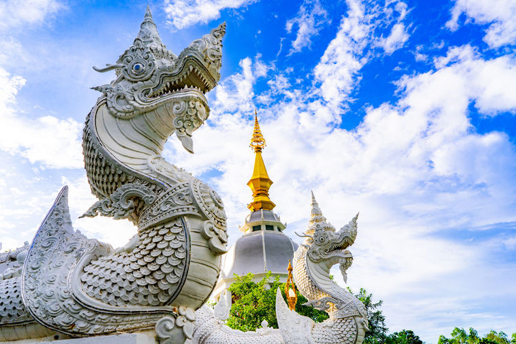 Low angle view of chinese dragon statues at temple against sky