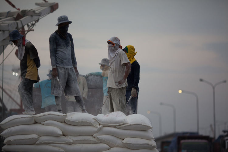 Men unloading cement bags at dockyard