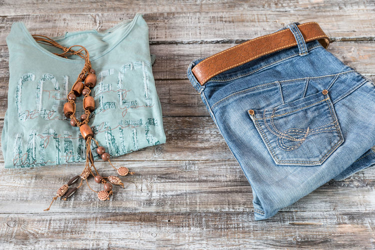 High angle view of top and necklace by jeans on wooden table