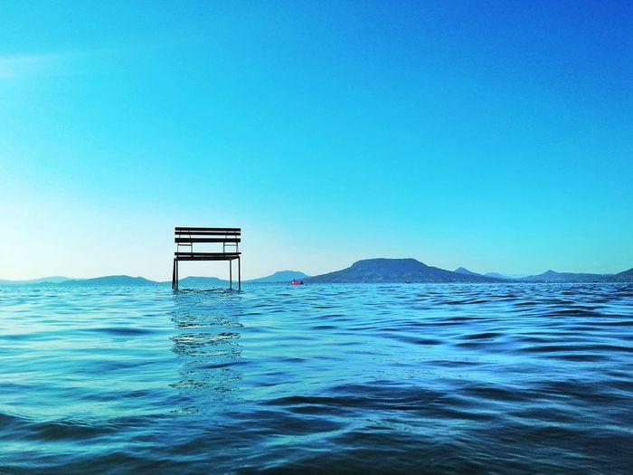 Lifeguard hut on sea against clear blue sky