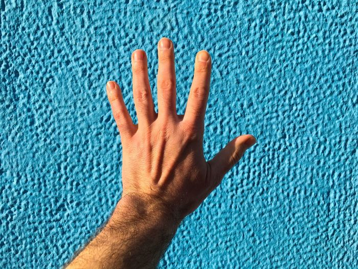 Cropped hand reaching towards blue wall