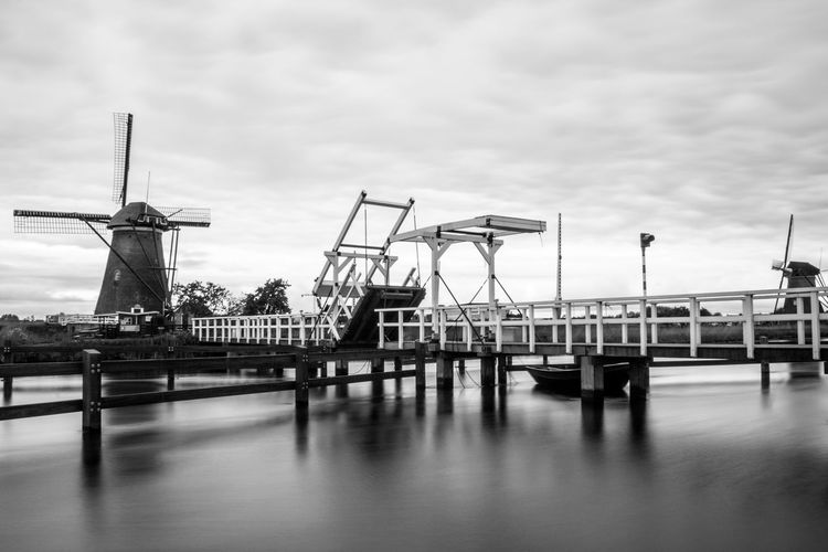 Windmill by pier over river against cloudy sky
