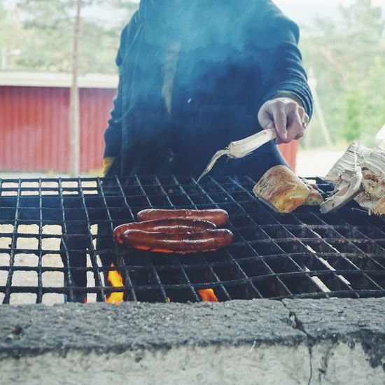 Midsection of man grilling sausages on barbecue at forest