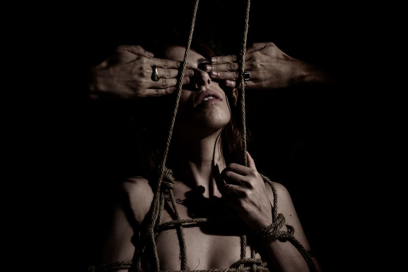 Cropped hand closing eyes of woman tied by rope against black background