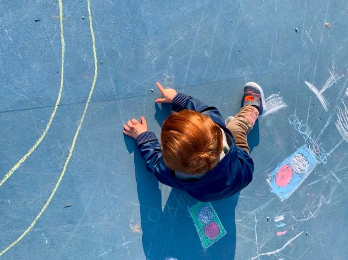High angle view of baby boy sitting in playground