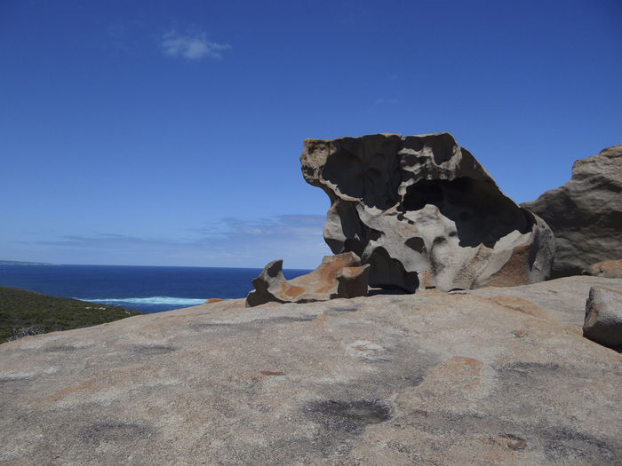 View of a rock formation in sea against blue sky
