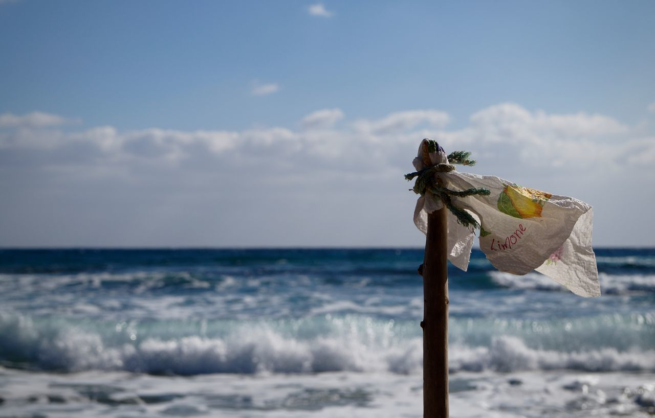 Flag Of Plastic And Wooden Pole By Sea Against Cloudy Sky