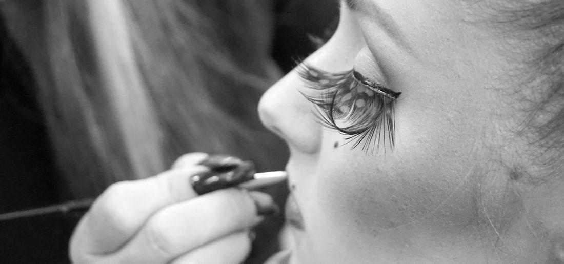 Midsection of female artist applying make-up on customer