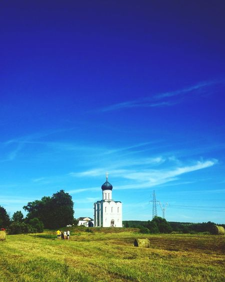 Lighthouse On Grassy Field Against Blue Sky