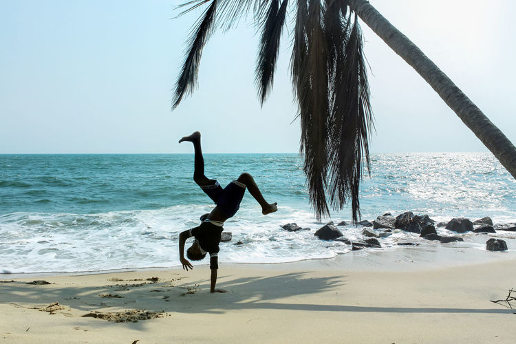 Hand stand on beach Handstand  Boy Teenager Teen Travel Kerala India Beach Sea Seashore Sky Nature Hanging Out Coconut Palm Tree People And Places