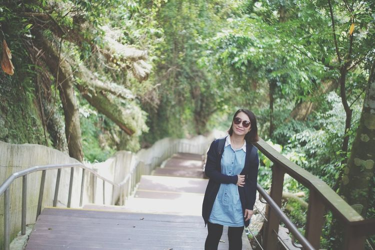 Woman standing amidst trees on steps