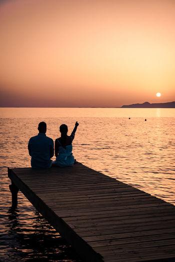 Men sitting on sea against sky during sunset
