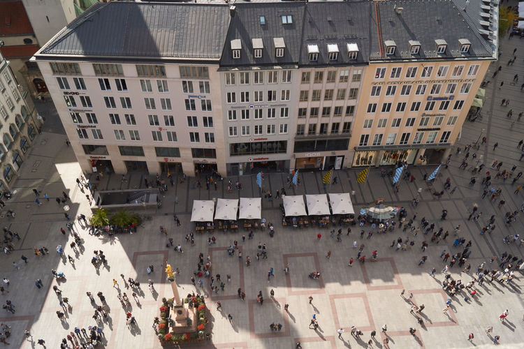 High angle view of people walking on street amidst buildings in city