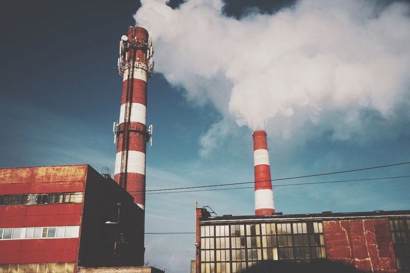 Low angle view of factory and smoke stack against sky