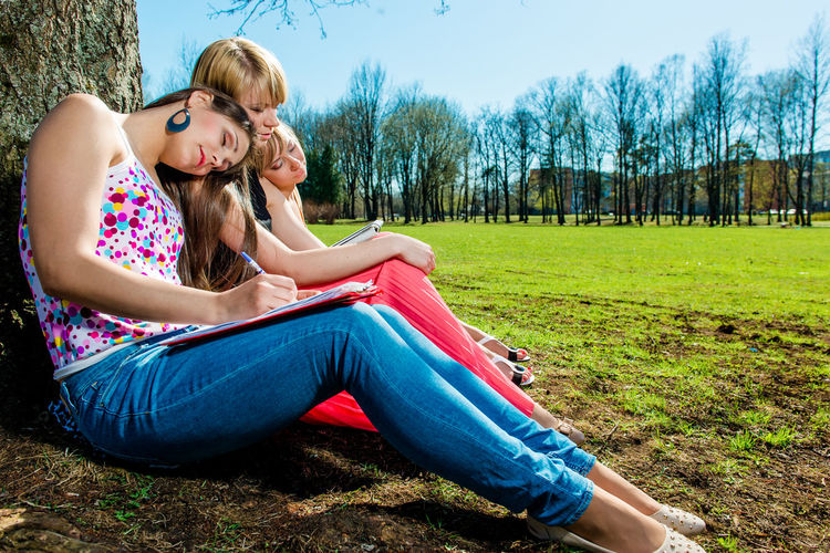 Young woman sitting on field in park