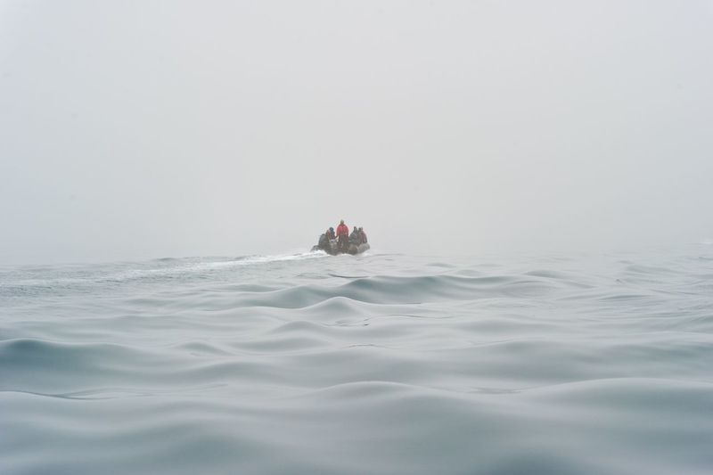 People in jet boat at sea against sky