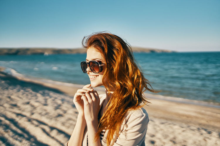 Young woman wearing sunglasses on beach against sky