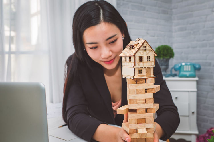 Businesswoman With Model Home On Block Removal Game At Desk