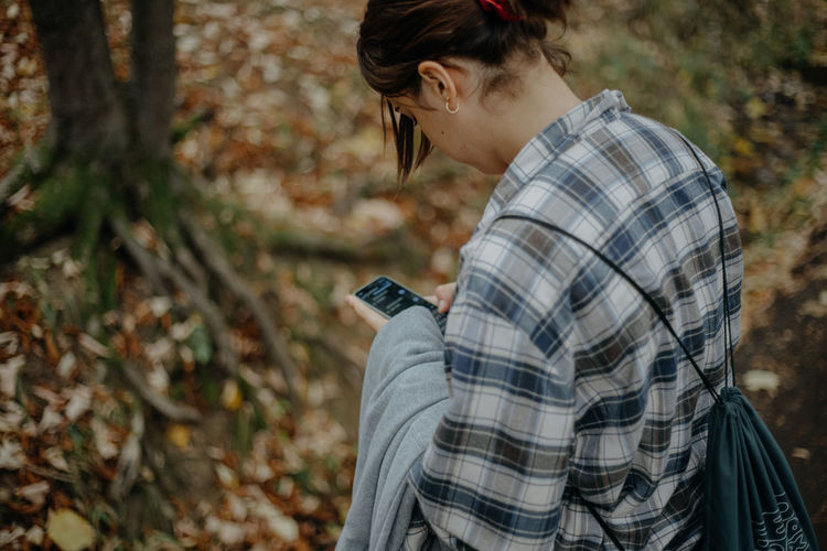 Midsection of woman using mobile phone in forest