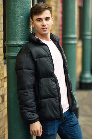 Young man standing in urban background with modern hairstyle. London, UK. One Person Looking At Camera Portrait Young Adult Clothing Real People Standing Three Quarter Length Casual Clothing Lifestyles Day Young Men Front View Architecture Focus On Foreground Black Color Wall - Building Feature Leisure Activity Architectural Column Beautiful Woman Hairstyle Leather