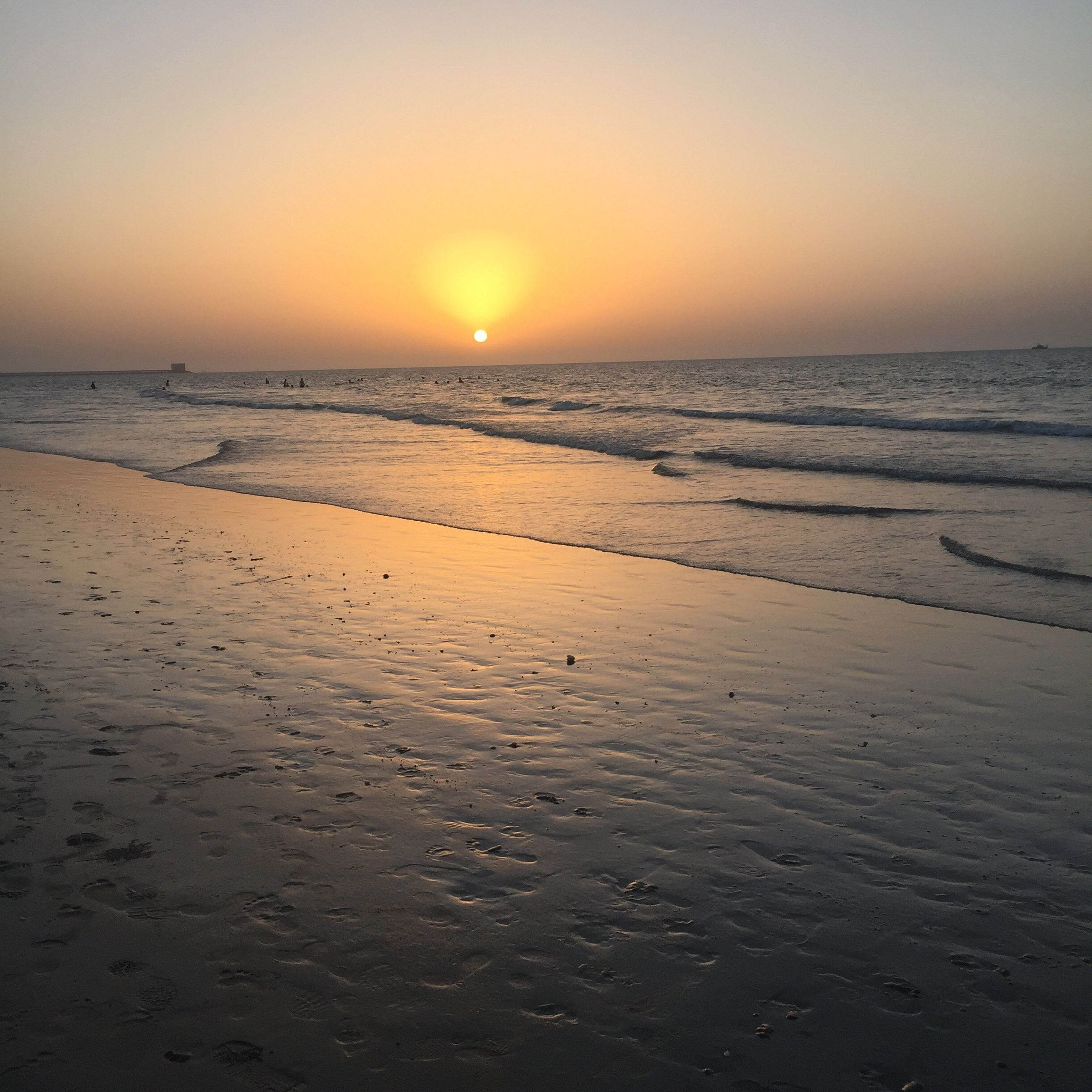 sunset, sun, sea, beach, scenics, water, tourism, tranquil scene, travel destinations, vacations, beauty in nature, majestic, atmosphere, horizon over water, tranquility, travel, idyllic, awe, vibrant color, wave, seascape, sand, non-urban scene, back lit, nature, atmospheric mood, shore, tide, environment, moody sky, coastline, glowing, dramatic sky, distant, sky