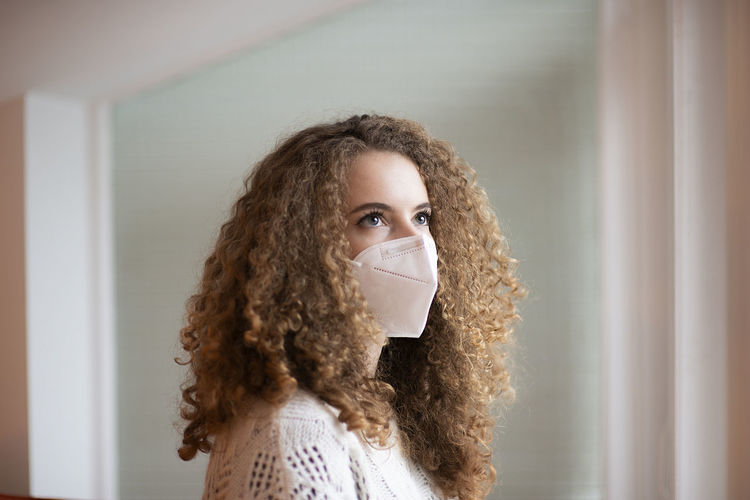 Portrait of young woman with curly hairs and sad eyes in white medical protective face mask